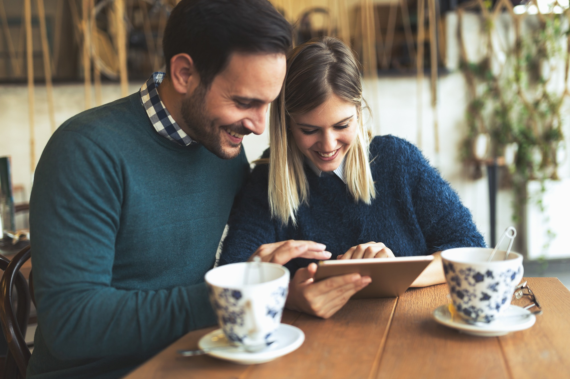 Young attractive couple using digital tablet in coffee shop