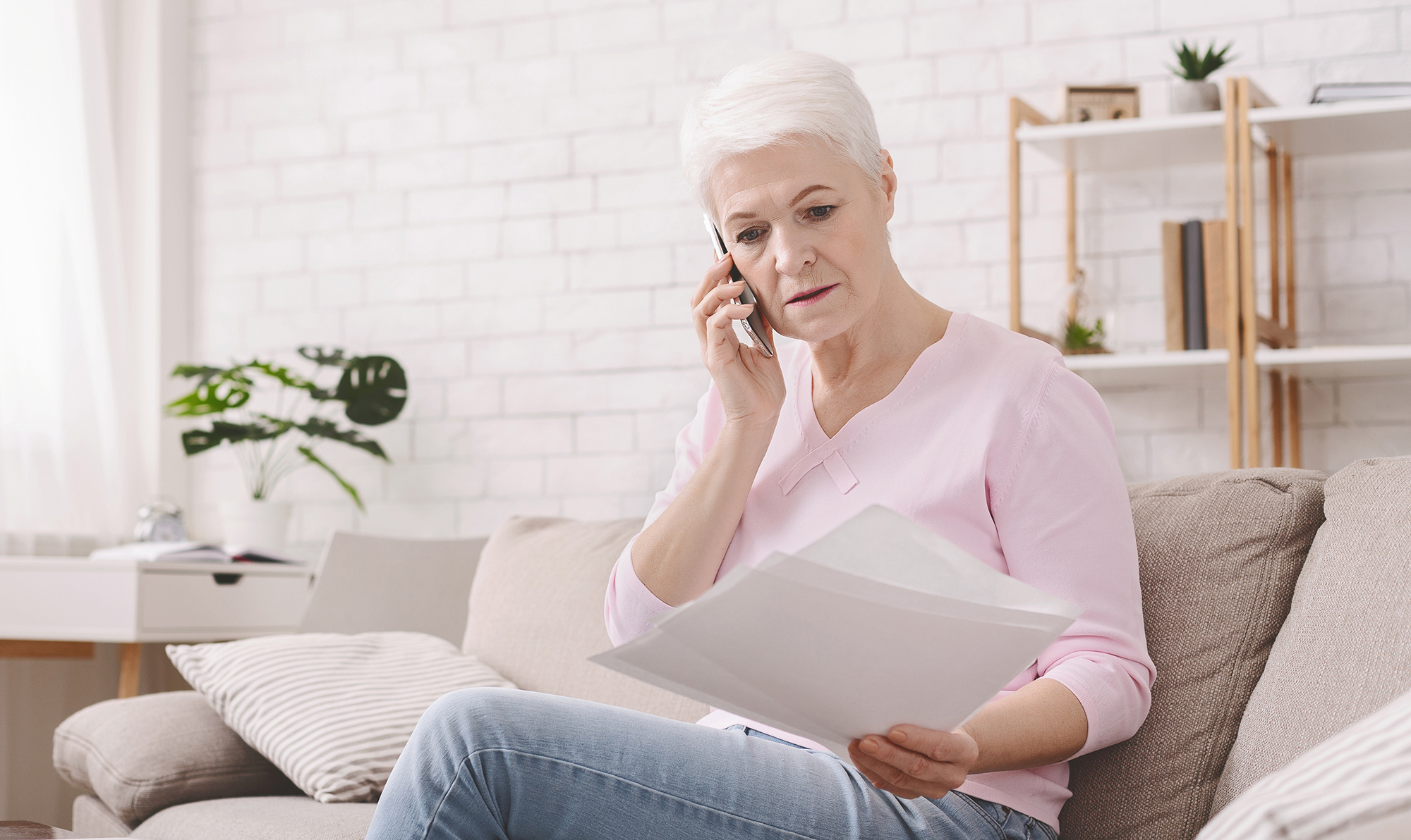 Shocked retired woman listening to bank agent with documents